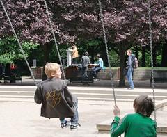 Schaukelnde Kinder bei der Marathonlesung am Platz der Bücherverbrennung. Im Hintergrund zwischen den Bäumen findet die Lesung statt.    (2006)