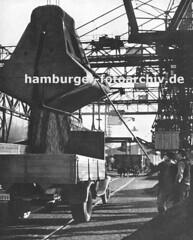 Kohlekai im Altonaer Hafen - Beladung eines Lastwagens. Im Hintergrund steht ein Güterwagen der Hafenbahn auf dem Gleis der Kaistrasse.