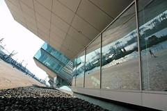Spiegelungen der Hafenschlepper in der Glasfassade.