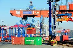 Portalkran bei der Bahnverladung eines Containers im Hamburger Hafen.