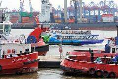 Hafenschlepper im Altonaer Hafen - eine Hafenfähre in Fahrt Richtung Anleger Neumühlen. Am gegenüber liegenden Elbufer das Container Terminal Burchardkai, ein Frachter liegt unter den Containerbrücken.