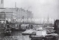 Alte Aufnahme vom Altonaer Holzhafen (ca. 1885). Beladene Schuten und ein Hausboot liegen geschütze zwischen Ponton und Kaimauer - Industriearchitektur direkt am Wasser.