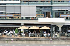 Mittagspause am Altonaer Hafenrand - Gäste sitzen auf einer Terrasse an den Tischen eines Restaurants.