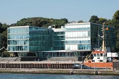 Modernes Bürogebäude - Hafenschlepper an seinem Liegeplatz in Neumühlen.