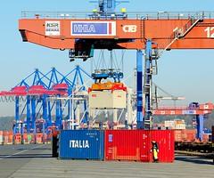 Ein Bahnkran, Portalkran hebt einen Container auf - HHLA Containerkran Burchardkai.