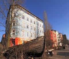 Mehrstöckige Wohngebäude an der St. Pauli Hafenstrasse. Holzboot am Strassenrand - farbige Hausfassaden.