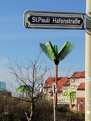 Strassenschild St. Pauli Hafenstrasse in der Sonne. Im Hintergrund die Metallpalmen des Antoniparks - Park Fiction.
