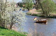 Blühende Bäume am Ufer der Lühe - ein Motorboot fährt flussaufwärts.