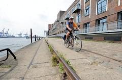 Schienen des Hafenkrans am Kai vor dem Altonaer Kaispeicher. Ein Fahrradfahrer fährt auf dem Kopfsteinpflaster die Kaianlage entlang.