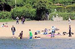 Hamburg im Sommer - Baden in der Elbe. Jugendliche am Elbstrand, einige liegen im Sand andere baden in der Elbe.