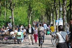 Dicht gedrängt gehen die Hamburger und Hamburgerinnen in der Frühlingssonne auf dem Weg entlang der Elbe spazieren. Dazwischen fahren Fahrräder - die Tische der Cafés am Elbufer sind besetzt.