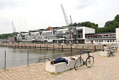 Mittagspause in der Sonne im Altonaer Fischereihafen. Am Hafenbecken des alten Altonaer Fischeihafens Hafenkräne und moderne Architektur.