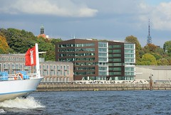 Elbuferbebauung - modernes Bürogebäude an der Grossen Elbstrasse. Auf dem Elbberg der Turm der Christianskirche - im Hintergrund der Hamburger Fernsehturm. Links der Bug eines Fahrgastschiffs der Hafenrundfahrt mit einer Hamburg Fahne.