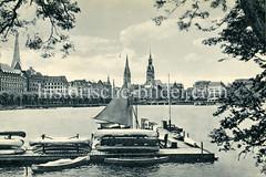 Historische Ansicht von der Binnenalster, Blick auf die Hamburger Altstadt; im Vordergrund Bootsverleih mit Kanus und Segelbooten.