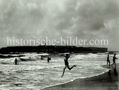 Baden am Strand - hohe Wellen, im Hintergrund die Hauptinsel Helgoland.