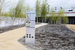 Eingang zum Lohsepark - Hinweisschild zum Gedenkort Hannoverscher Bahnhof - im Hintergrund die Bahntrasse mit Lokomotive.