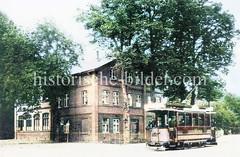 Altes Schulgebäude bei der Kirche am Marktplatz von Hamburg Niendorf; eine Straßenbahn fährt vorbei..