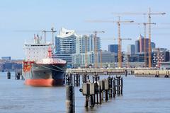 Bilder aus dem Hamburger Stadtteil Hafencity. Ein Auflieger liegt an den Dalben in der Norderelbe - Baukräne am Strandhafen.