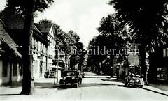 Historische Ansicht von Ludwigslust, Mecklenburg-Vorpommern; Blick in die Sandstraße mit parkenden Autos, Straßenbäume (ca. 1935).