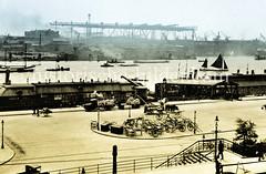 Blick auf die St. Pauli Landungsbrücken - Handkarren, Pferdefuhrwerk und Lastwagen  stehen bereit;  am anderen Elbufer Werftanlagen   (ca. 1923)..