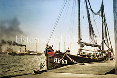 Fischkutter HF 65 am Ponton Fischmarkt Altona - im Hintergrund fährt ein Raddampfer unter Dampf auf der Elbe  (ca. 1923).