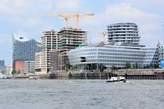 Fotos aus dem Hamburger Stadtteil Hafencity; Baustellen / Neubauten mit Baukränen am Strandkai - im Vordergrund das Unilever-Gebäude, im Hintergrund die Elbphilharmonie.