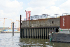 Einfahrt, Schild Südwesthafen im Hamburger Stadtteil Grasbrook - im Hintergrund Baukräne in der Hafencity.