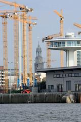 Das Hamburger Wahrzeichen, die Michaeliskirche zwischen Baukränen in der Hafencity.