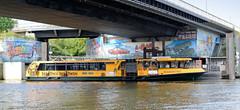 Die Hafenfähre hat am Fähranleger Argentinienbrücke in Hamburg Steinwerder angelegt; die Betonwände der Brücke sind mit Graffiti versehen.