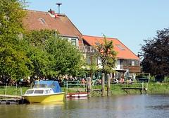 Gartencafé am Ufer der Este im Alten Land. Motorboote liegen am Schlengel am Ufer des Flusses.