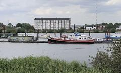 Blick über den Holzhafen in Hamburg Moorfleet - auf der gegenüber liegendes Seite der Moorfleeter Deich und die typische Industriearchitektur eines Lagergebäudes. An den Bootsstegen des ehemaligen Laufs der alten Elbe sind Boote vertäut.