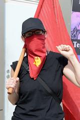 """Demonstration """"Wer hat der gibt"""" in Hamburg Blankenese am 21.08.21; Kämpferin mit Roter Fahne - Schal Hammer + Sichel."""