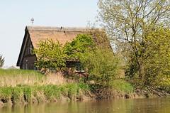 Am Lauf der Este stehen viele reetgedeckte Häuser am Ufer des Flusses.