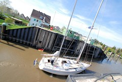 Durchfahrt eines Segelboots durch das innere Sperrwerk im Hamburger Stadtteil Cranz. Auf Anforderung wird die Fussgängerbrücke zurückgefahren, damit Schiffe mit hohen Masten das Sperrwerk passieren können.