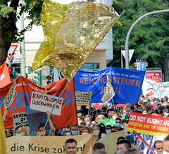 """Demonstration """"Wer hat der gibt"""" in Hamburg Blankenese am 21.08.21; Demonstrationzug mit Transparenten - Kapitalismus überwinden."""