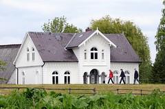 Historische Gründerzeit-Architektur - Spaziergänger auf dem Deich. Neben alten prunk- vollen Altenländer Bauernhäusern sind im Alten Land auch sehr schöne Wohnhäuser im Architekturstil der Gründerzeit entstanden. Neben reichhaltigem Stuckdekor an der