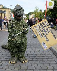 """Demonstration """"Wer hat der gibt"""" in Hamburg Blankenese am 21.08.21; Dinosaurier mit Fahne - Wir können uns die Reichen nicht mehr leisten."""