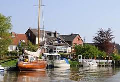 Ausflugsziel im Frühling - Altes Land bei Hamburg Cranz. Die Este im Alten Land ist ein beliebtes Sportboot-Revier. Segelboote und Motorboote liegen am Ufer des Flusse.