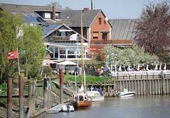 Gartencafé unter blühenden Kirschbäumen im Hamburger Stadtteil Cranz. Mehrere Sportboote liegen an einem Schlengel - die Este ist ein beliebtes Sportbootrevier.