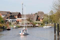 Segelboote fahren unter Motor auf der Este Richtung Elbe. Die Boote habe gerade das innere Estesperrwerk durchfahren - Gäste eines Cafés sitzen am Ufer der Este.