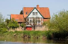 Wohnhaus zwischen Bäumen am Ufer der Este.