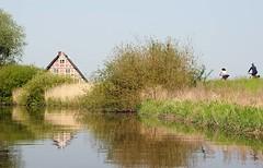 Fachwerkhaus am Ufer der Este. Fahrradfahrer_in auf dem Deich des Flusses - die Tour entlang der Este ist ein beliebtes Ausflugsziel auch für Hamburger.